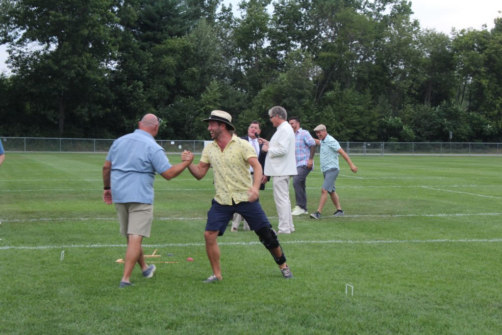Two men shaking hands excitedly on the croquet field at Croquet on the Green 2019