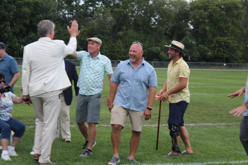 Two men high fiving with two other men laughing next to them at Croquet on the Green 2019