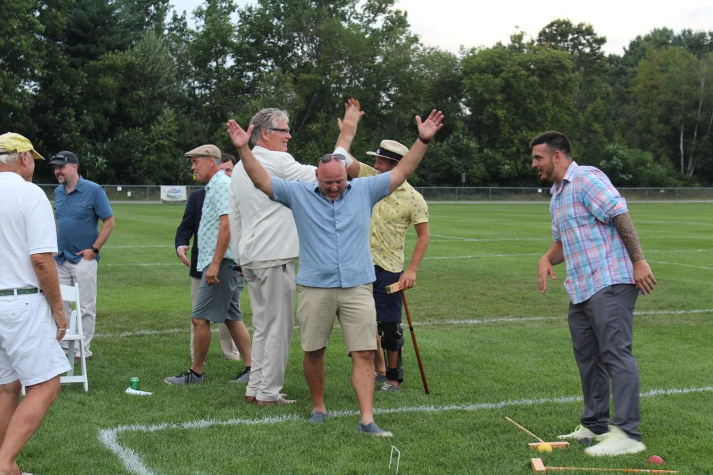 Man throwing his hands into the air while two other men high five in the background at Croquet on the Green 2019