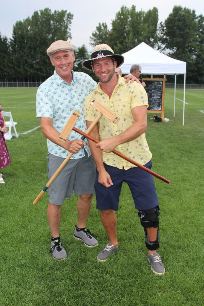 Two men holding croquet mallets in an X shape at Croquet on the Green 2019
