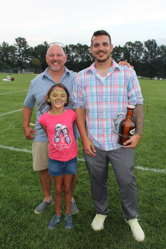 Two men and a young girl with dragon face paint on smiling together at Croquet on the Green 2019