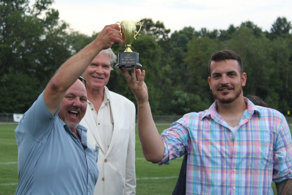 2nd place winners of croquet, Bob Wiltsie and Matt Stevens holding their trophy in the air with Walt Adams looking on in the background at Croquet on the Green 2019