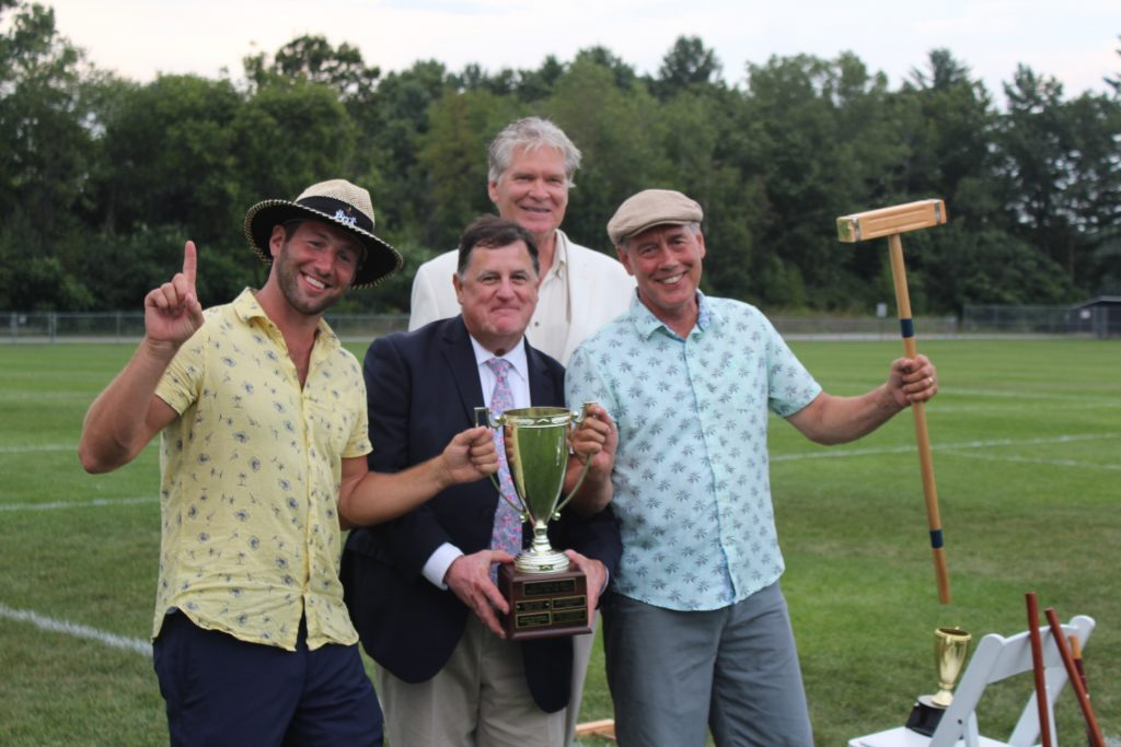 Winners of croquet, Brett and Brett Jr. Armstrong, holding trophy, mallet, and one finger up, with Chris Lyons and Walt Adams at Croquet on the Green 2019