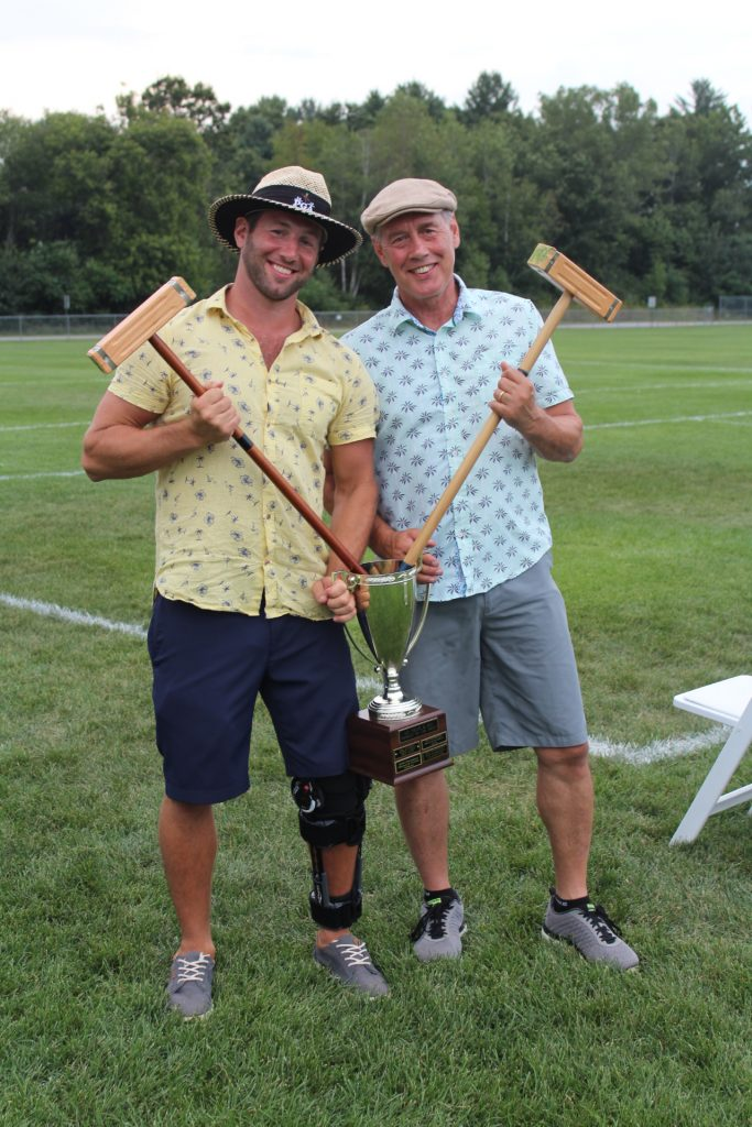 Croquet tournament winners, Brett and Brett Jr. Armstrong, holding mallets sticking out of big trophy at Croquet on the Green 2019