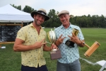 Croquet winners, Brett and Brett Jr. Armstrong, holding two trophies, a croquet mallet, and two fingers up at Croquet on the Green 2019