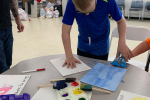 kid painting at table