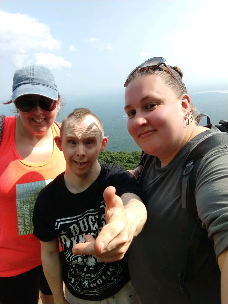 Group of three people, one with disability, at the top of a mountain