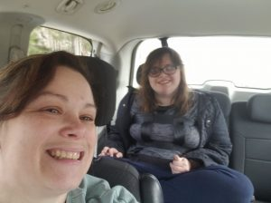 Stacie in front seat of car with young woman in back seat of car smiling