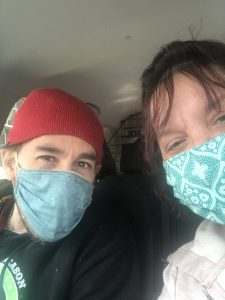A man and a woman sitting in a car wearing teal colored masks