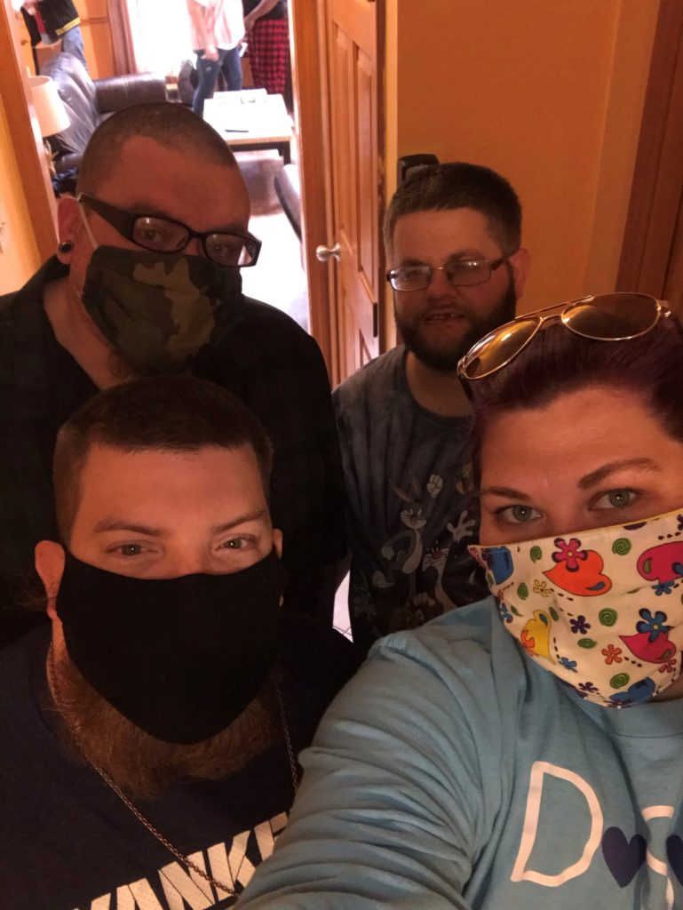 Women in blue shirt with facemask taking selfie with three males