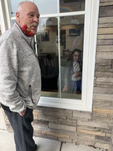 Older man standing outside window with his elderly mother inside