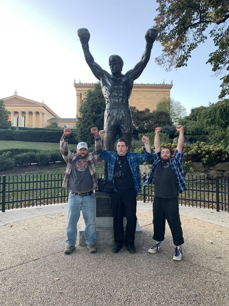 Three man standing in front of the Rocky statue in Philadelphia, PA with their hands all up in the air