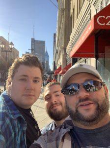 Three men taking a selfie on a sidewalk in Philadelphia, PA