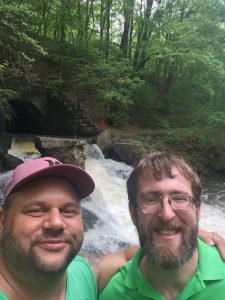 Matt on the left with John in green shirts in front of a waterfall