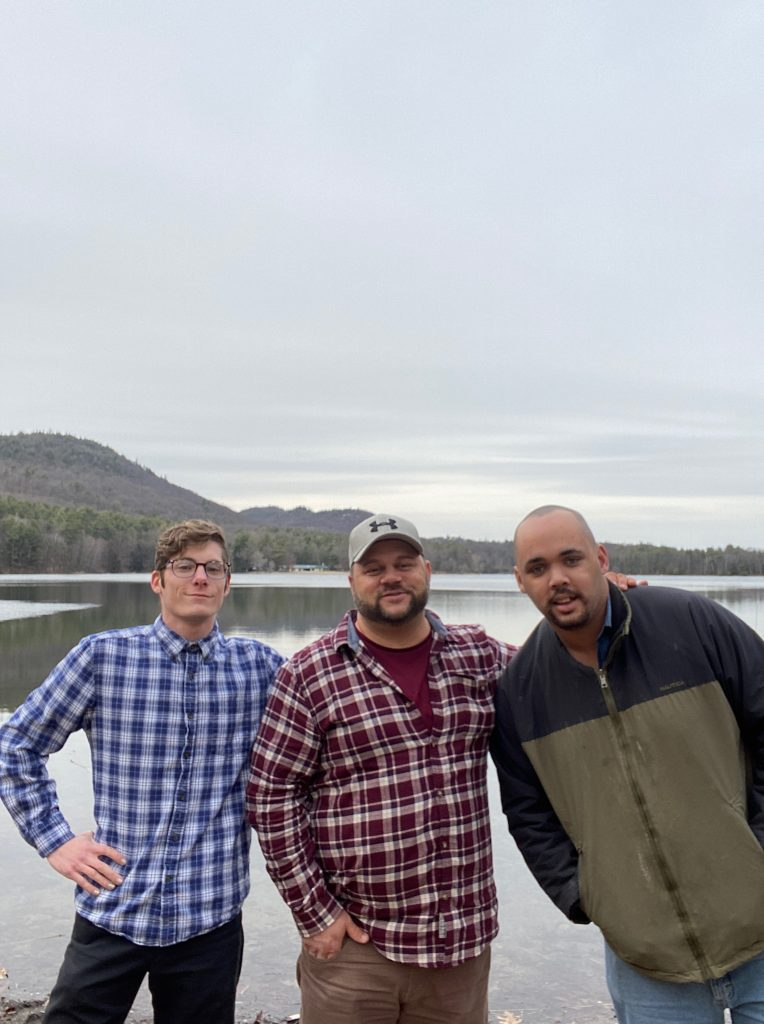 Three men standing together in front of a lake