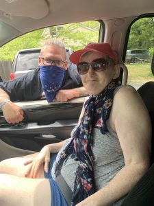 Woman sitting in car with man hanging in window with mask