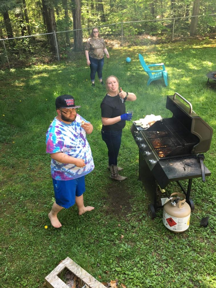 man in tie-dye shirt with woman sticking her tongue out and giving thumbs up in front of a bbq grill
