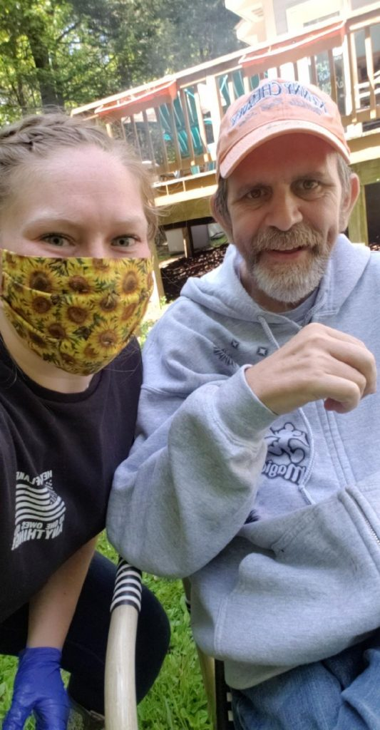 Woman with yellow patterned mask taking a selfie with an older man in a grey zip-up hoodie