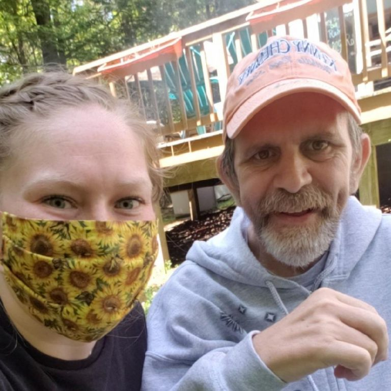 woman with yellow flower mask sitting with older man with beard