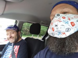 Two men sitting in a car, one with a big beard wearing a mask and another with a hat smiling