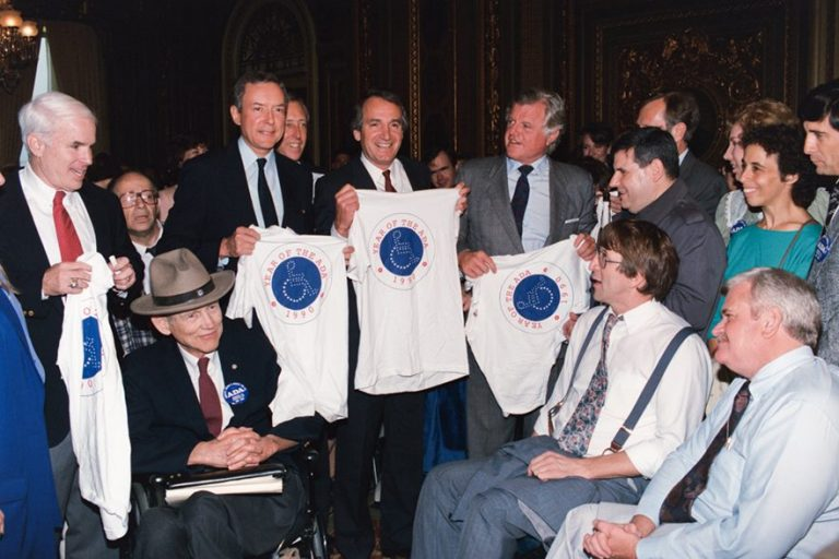 "Tom Harkin with group of people holding t-shirts that say ""year of the ADA"" photo credit: https://harkininstitute.drake.edu/wp-content/uploads/sites/103/2017/08/ADA_Harkin_.png"