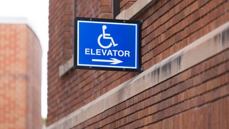 Handicap symbol with text elevator and arrow on brick building