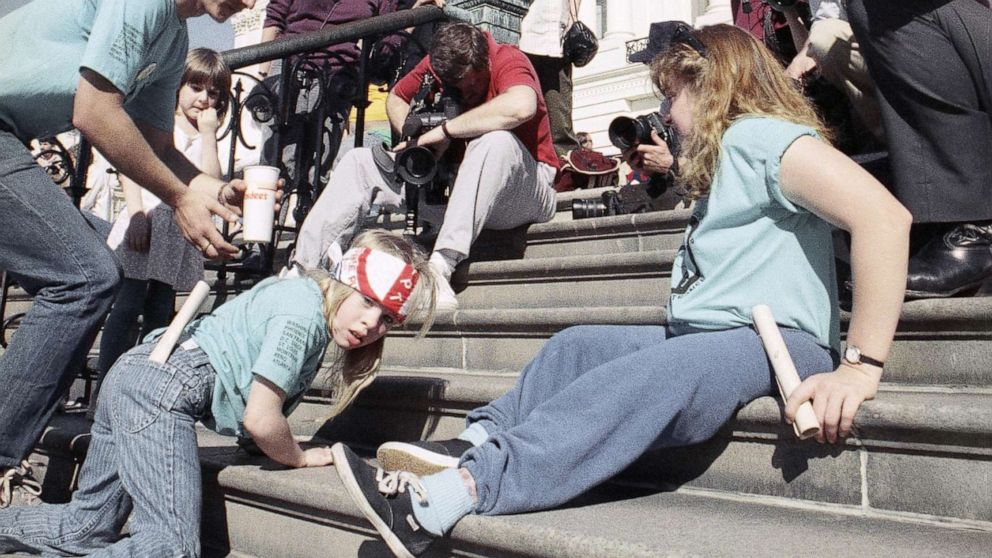 child crawlign up steps with adults doing the same nearbyPhoto credit: https://abcnews.go.com/US/30th-anniversary-disability-civil-rights-protest-advocates-push/story?id=694914