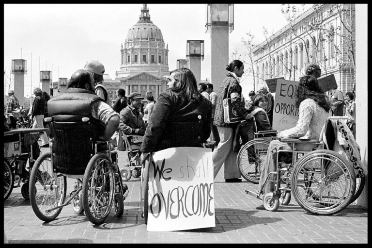 "Group of people in wheelchairs protesting with sign ""we shall overcome""Image credit: rectoremeritus.org"