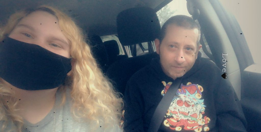 women with curly blonde hair wearing mask in car with older man
