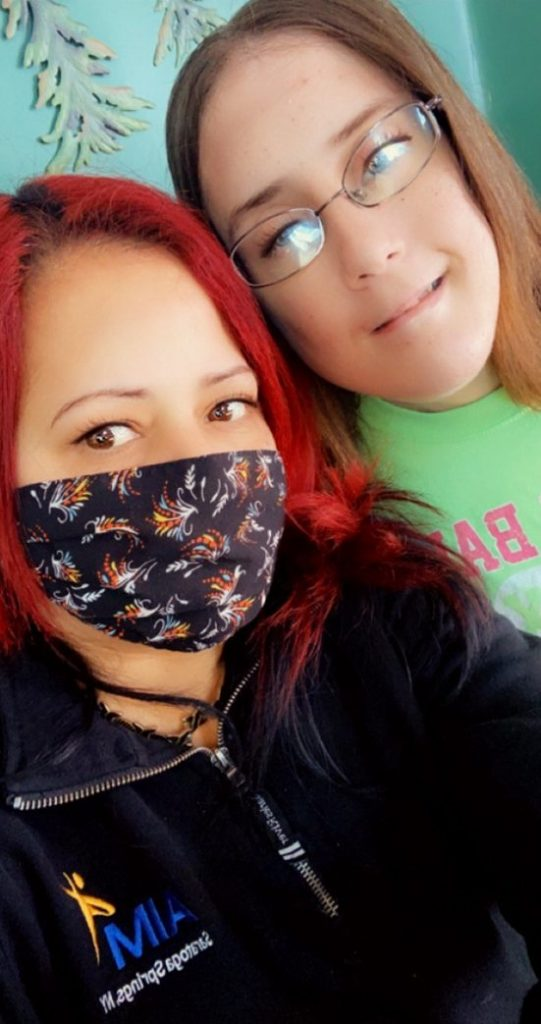Women with bright red hair and masking taking a selfie with a girl with glasses