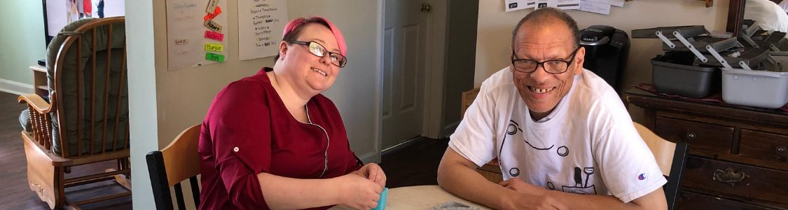 Woman with pink hair in maroon top sitting with man in glasses and a white shirt