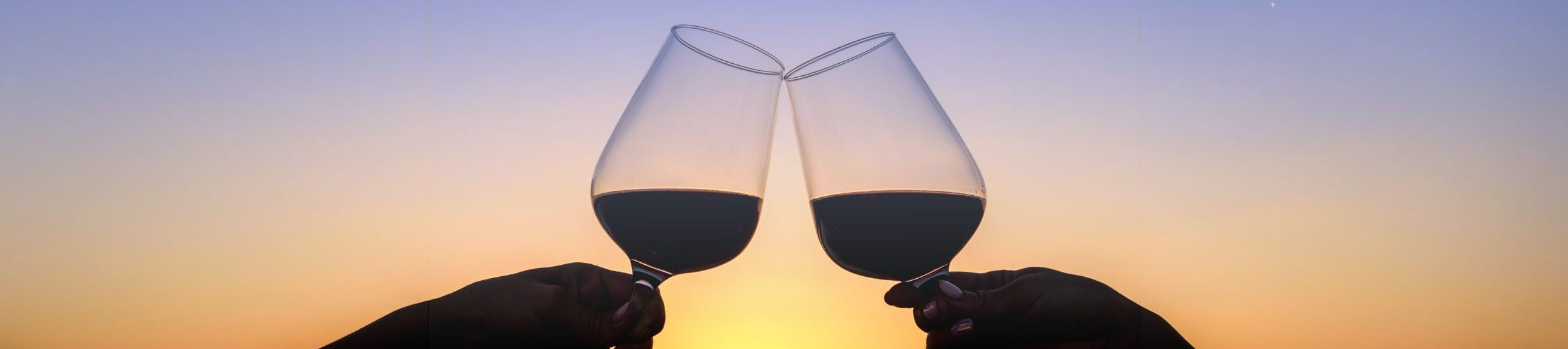 Image of two wine glasses cheersing over sunset