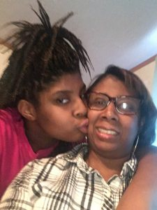 Latoyia smiling with daughter kissing her cheek