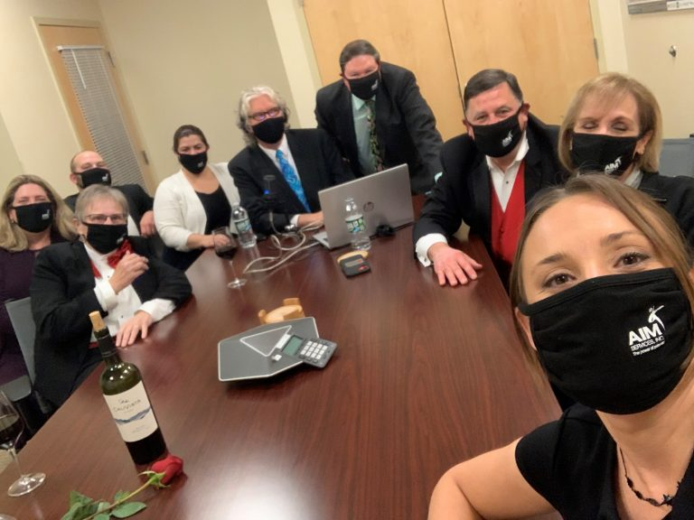 Group of people wearing black face masks all sitting around a table