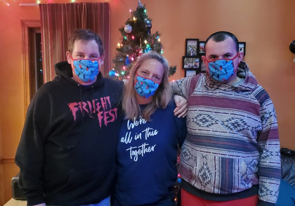 Woman between two men all wearing the same face mask