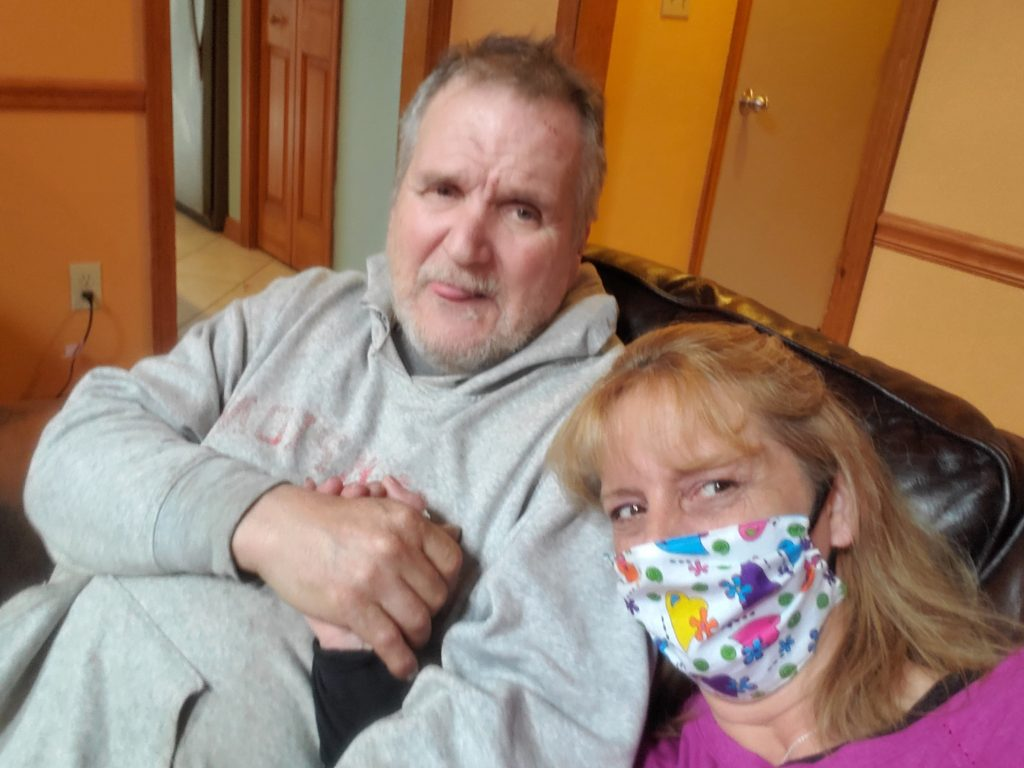 woman in colorful face mask holding hands with older man in a grey sweatshirt