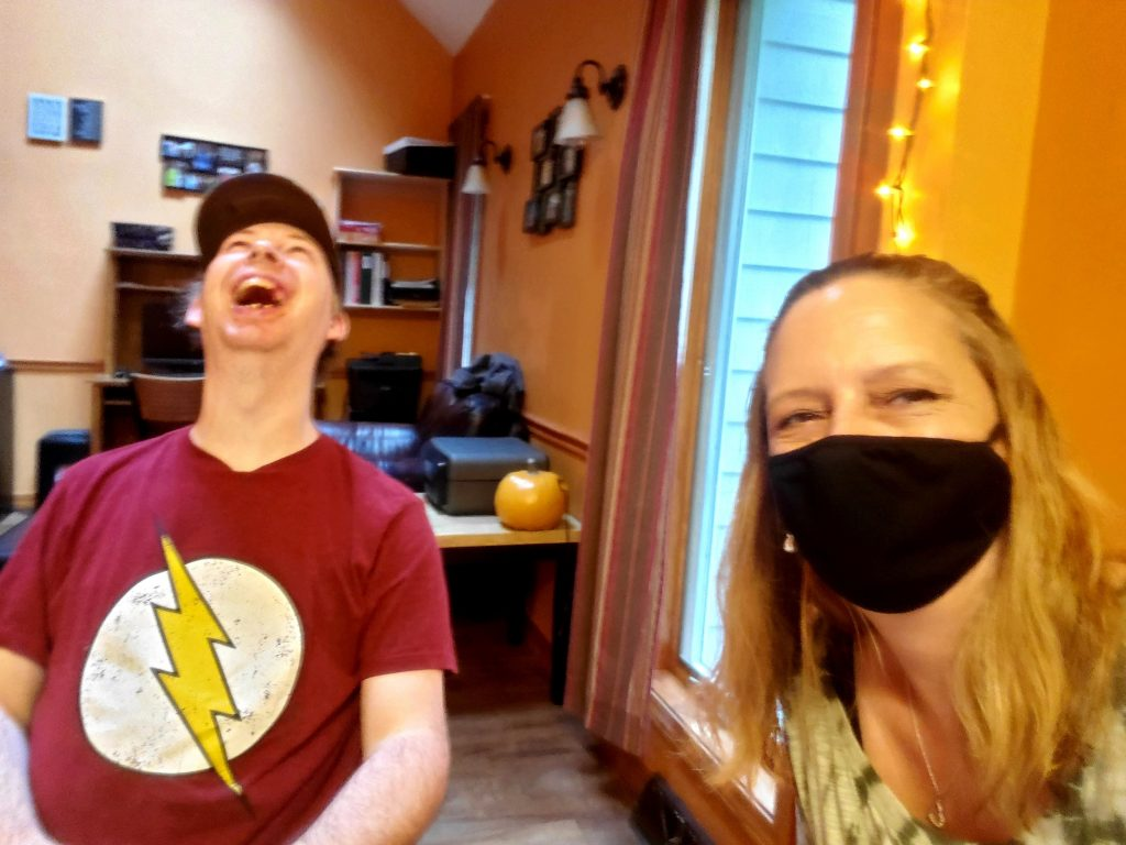 woman with black mask sitting next to man with lightning bolt in his shirt and throwing his head back in laughter