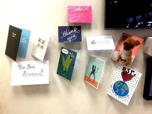 a bunch of different greeting cards pinned to a wall