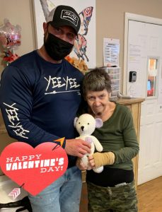 Man with mask standing with woman holding a teddy bear