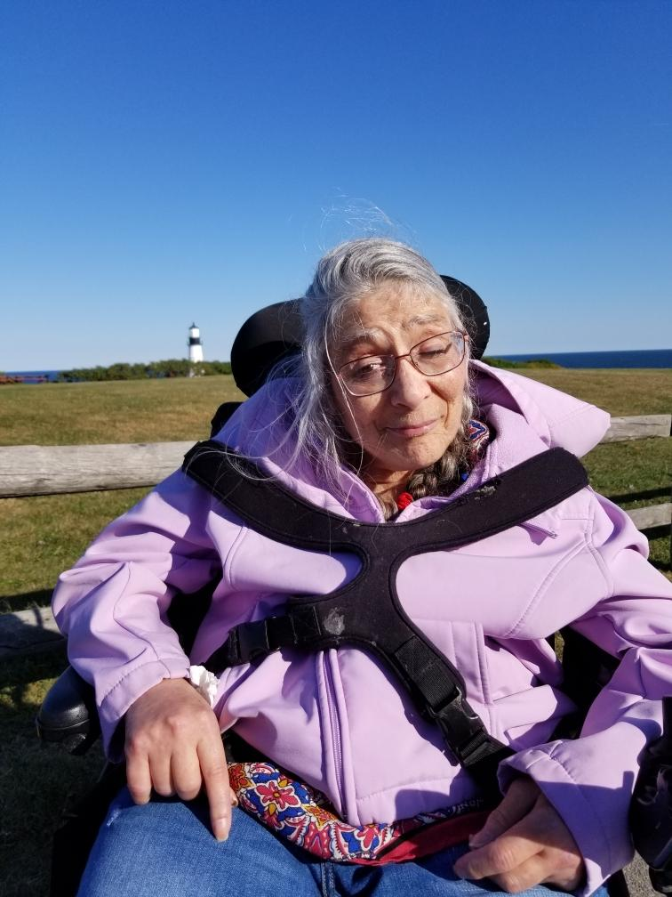 Woman in a light purple hoodie in a wheelchair outside with a bright blue sky