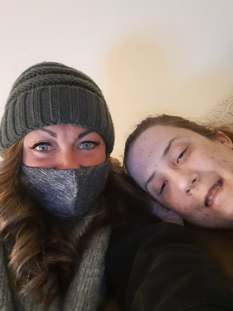 Woman with blue eyes and face mask with girl smiling