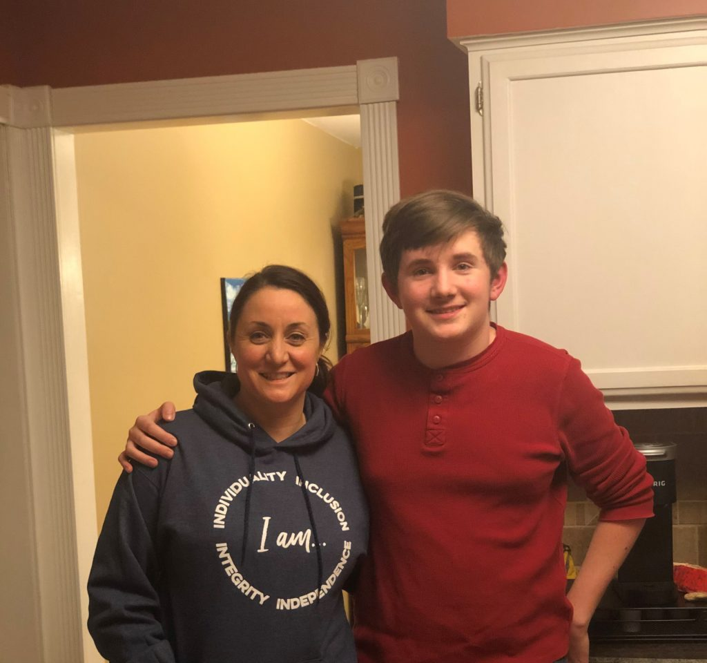 Tara Pleat in an I AM AIM hoodie with her son
