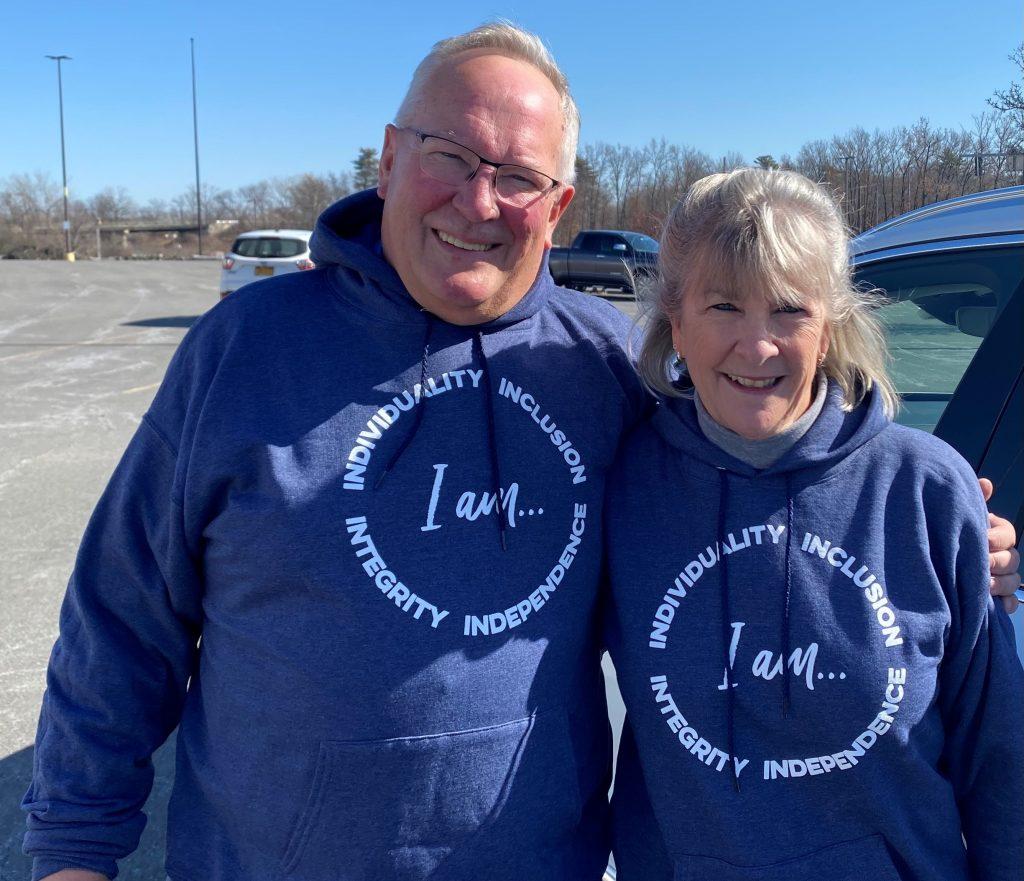 Tom and Beth Flynn wearing I AM AIM hoodies