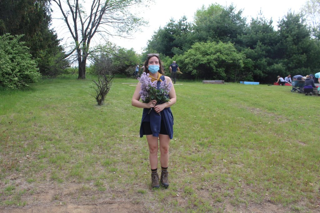 Molly standing in a field holding flowers