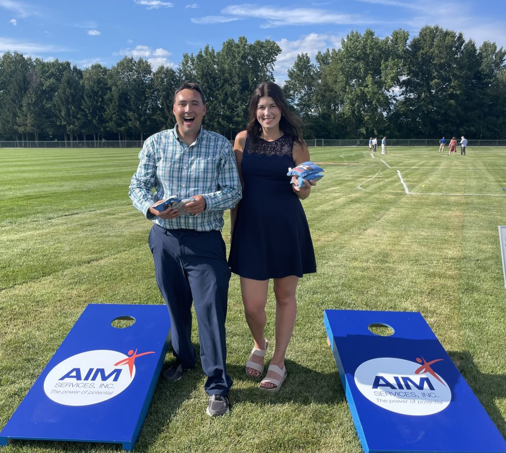 Two people holding cornhole bags smiling and standing next to two bright blue cornhole boards with the AIM logo on them at AIM Services Croquet on the Green 2021