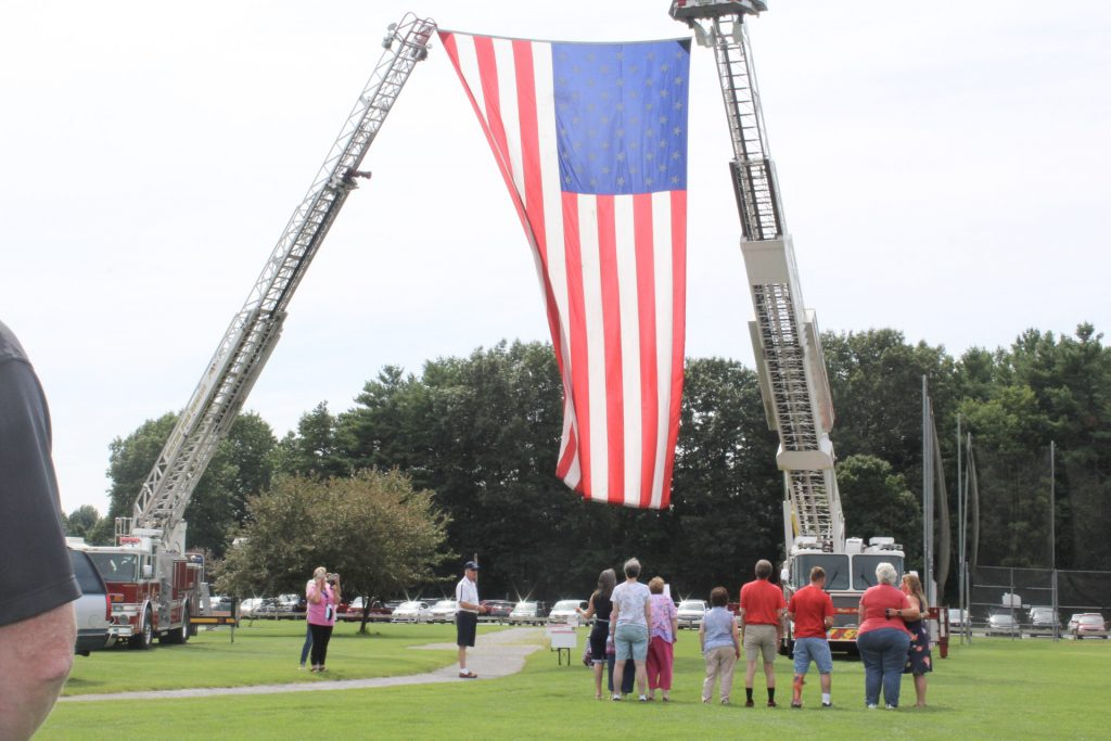 Group of people facing a large American flag held up by two fire trucks at AIM Services Croquet on the Green 2021