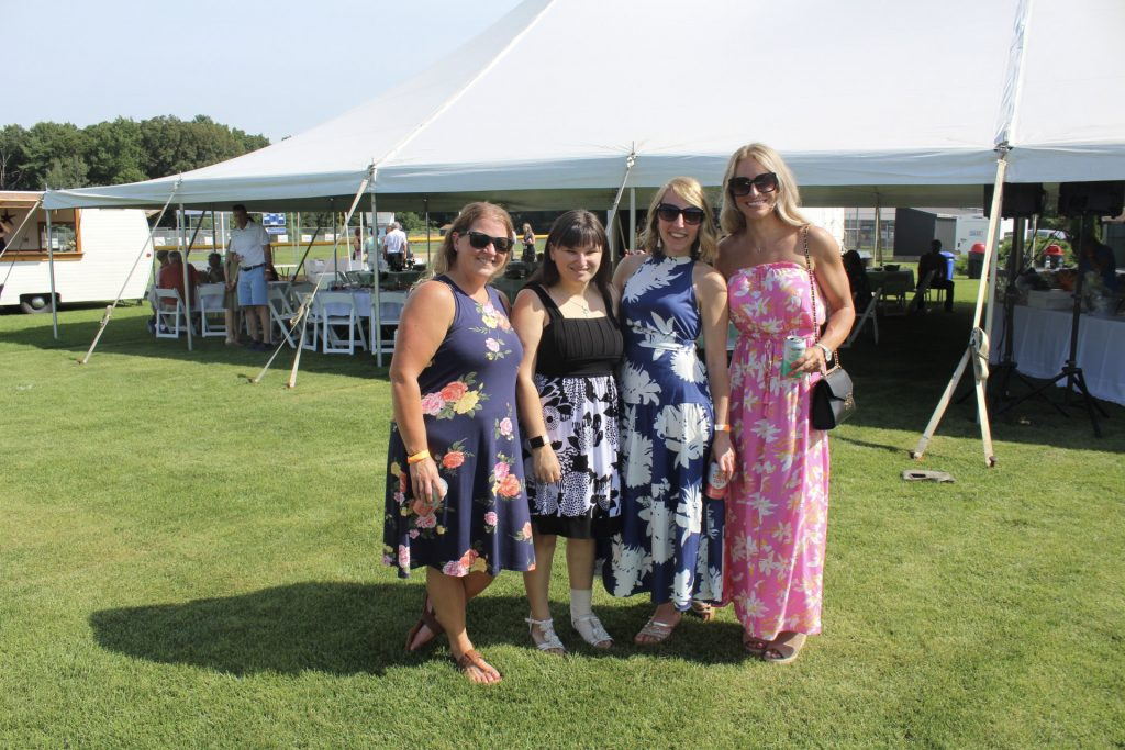 Group of four women, all in pattern dresses, at AIM Services Croquet on the Green 2021