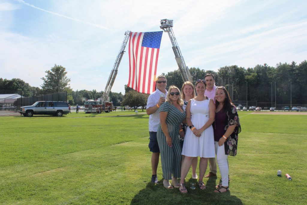 Group of 6 people standing together and smiling in front of large American flag at AIM Services Croquet on the Green 2021