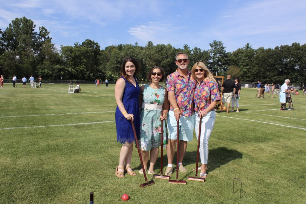 Group of four people on a croquet field, two of them are wearing matching Hawaiian shirts at AIM Services Croquet on the Green 2021