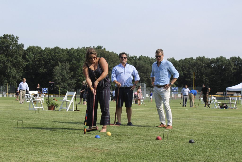 Women in a navy jumpsuit playing croquet while two people in blue dress shirts watch at AIM Services Croquet on the Green 2021